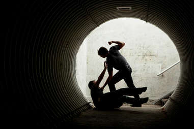 Man being mugged and hit in dark tunnel