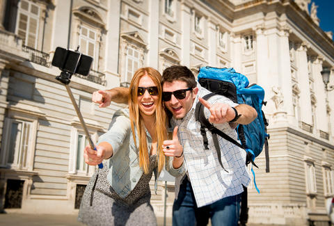 man and woman using selfie stick on vacation