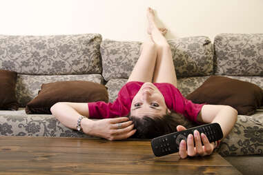 Girl laying face down on couch with remote controller