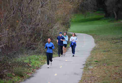 Group of adults running on outside trail