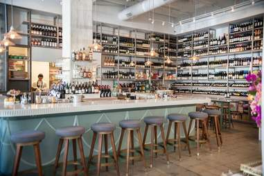 stools lined up at the bar at esters wine shop