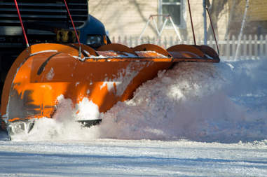 Orange plower moving snow from main road