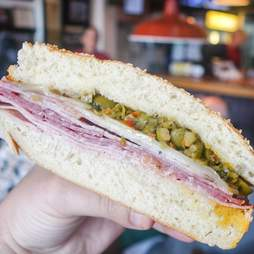 Hand holding Muffaletta sandwich filled with giardiniera