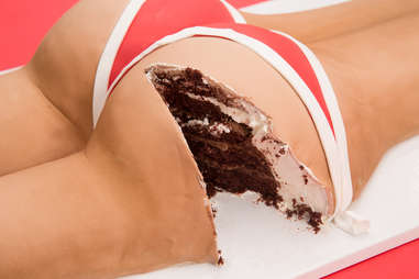 Chocolate erotic cake with slice taken out