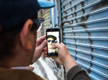 Man snapchatting by graffiti