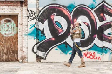 Portrait of rapper Anthony Bunch walking near graffiti wall