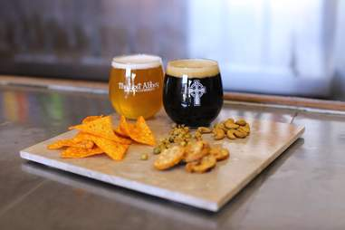 Full glasses of Lost Abbey beer with snacks
