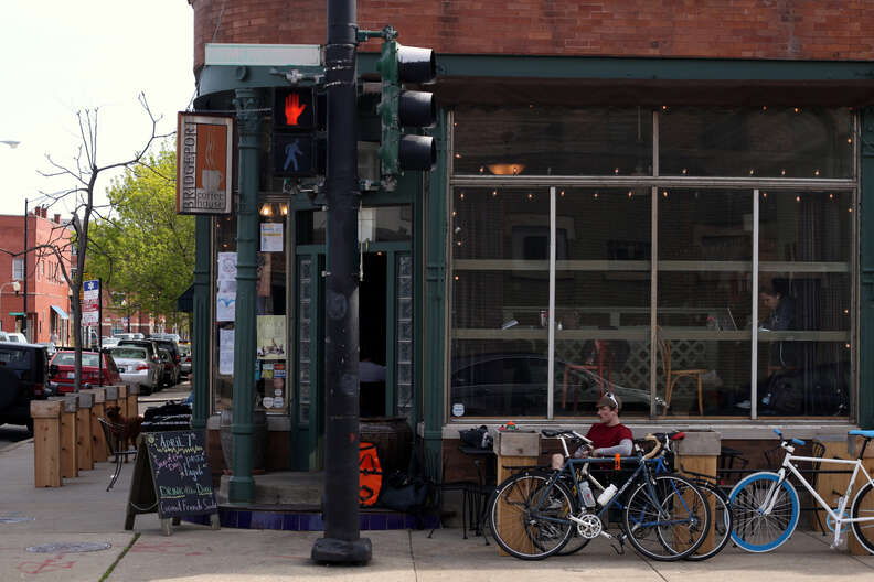 Man sitting in front of the store, next to bikes