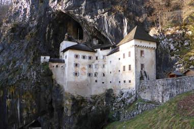 Predjama castle built into grassy corner Slovenia's landscape