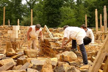 Men in reenactment costumes constructing castle