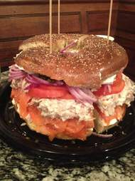 Large bagel crammed with lox, cream cheese, and tomato slices