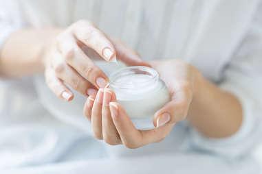 woman with jar of moisturizer