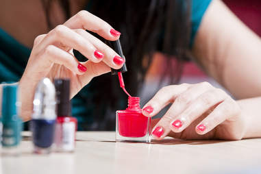 woman painting her nails with nail polish