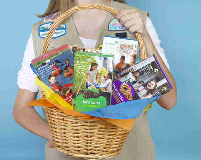 Girl scout carrying a basket full of Girl Scout Cookie boxes