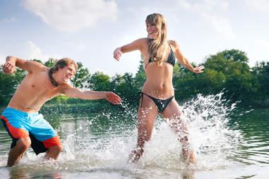 man and woman splashing in lake