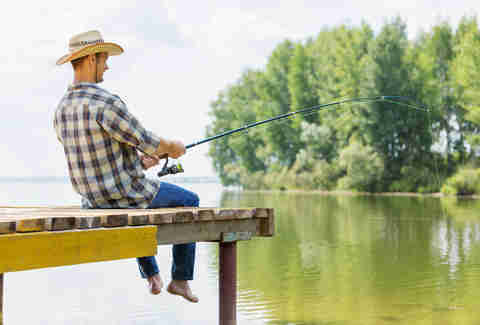 man in cowboy hat and plaid fishing