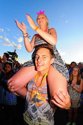 woman sitting on man' shoulders at a concert or music festival