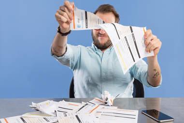 man tearing up phone bills