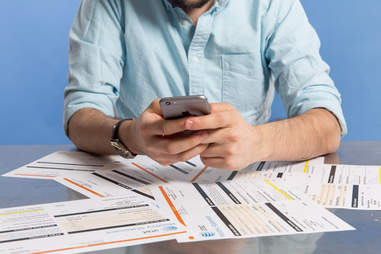 man using iphone 6 above a pile of phone bills
