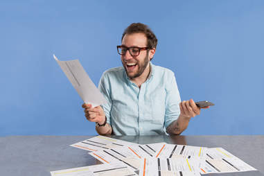 man looking happy with iPhone in hand and phone bill in other hand