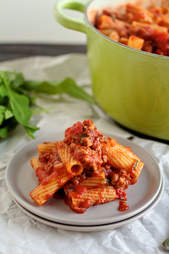 Spicy tomato pasta with sausage and crushed tomatoes on white plate