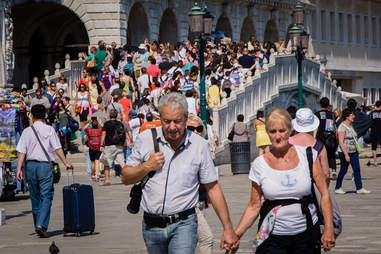 tourists holding hands in italy