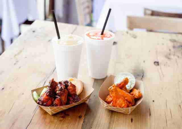 Beverages and small paper containers of barbecued chicken