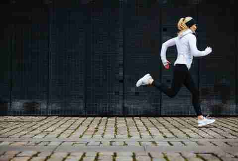 woman jogging on a cobble stone street