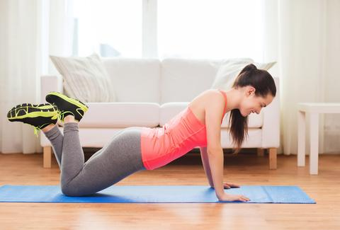 Woman Doing A Push Up In Apartment Living Room Exercise Routine