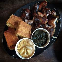 Platter of corn bread, collar greens, and BBQ bits