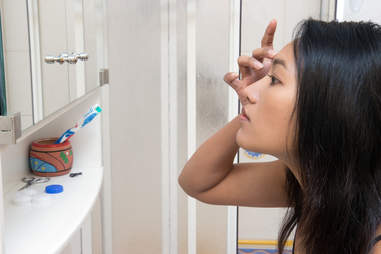 Woman picking at her face in front of mirror
