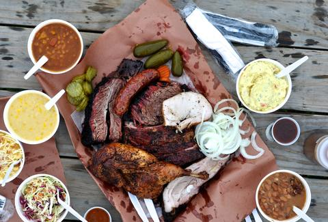 barbecue platter with beef, chicken, ribs, pickles, beans, onions and cole slaw