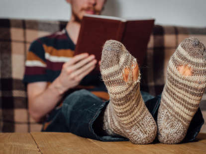 Man with holey socks sitting on couch