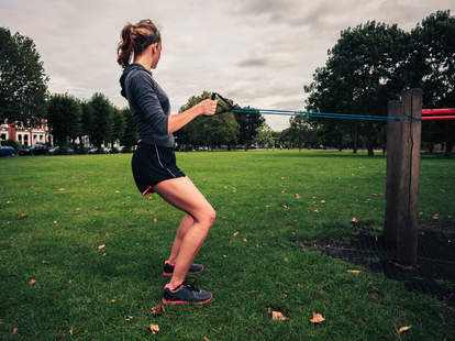 woman exercising outside with a resistance band
