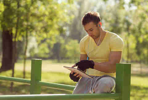 man working out outside with tablet