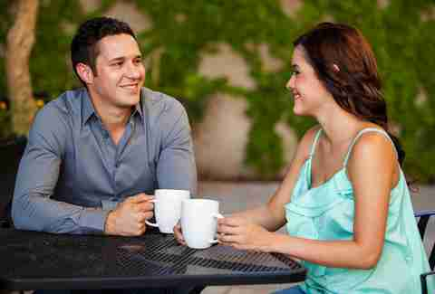 Couple drinking coffee and smiling on their first date at a restaurant