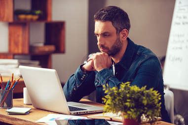 a man looking at his computer and working concentrating intensely