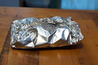 Item wrapped in aluminum foil placed on table