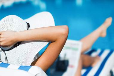 woman relaxing on the beach and sunbathing and reading