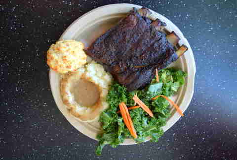 A neat gathering of ribs, kale salad, and a biscuit on a paper plate