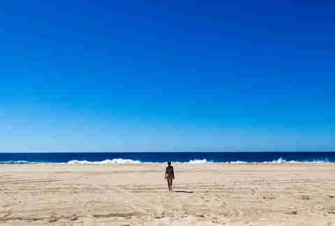 person walking on beach in todos santos