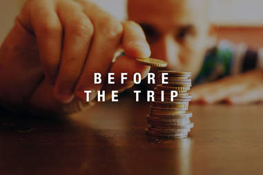 man counting coins and saving money for trip