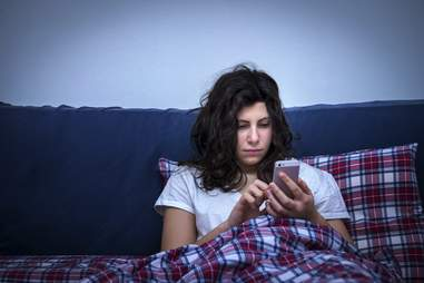 Girl using smartphone in bed at night