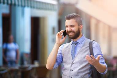 a well dressed man talking on the phone in a city