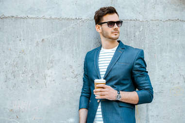 a well dressed stylish young man wearing a suit and sunglasses