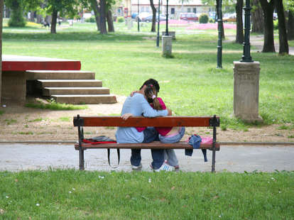 couple kissing on a bench outside
