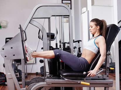 women on gym machine working legs
