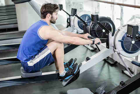 man using rowing machine at gym