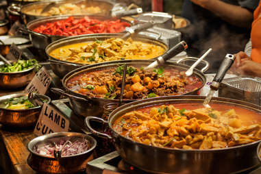 spicy Indian dishes being served in pots and pans