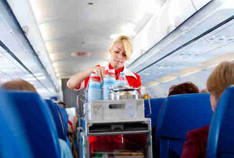 airline flight attendant with food and drink cart